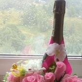 Подарочное украшение шампанского цветами с конфетами